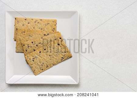 Flax Chips On The White Square Plate Above White Marble Background