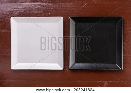 Flat Lay Above Black And White Square Plates On The Wooden Boards Table