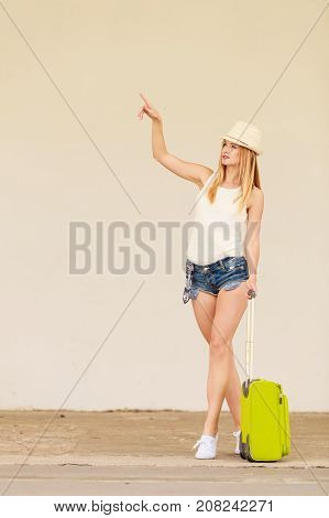 Travel adventure teenage journey concept. Woman wearing denim shorts white top and sun hat suitcase holding suitcase on wheels pointing at something