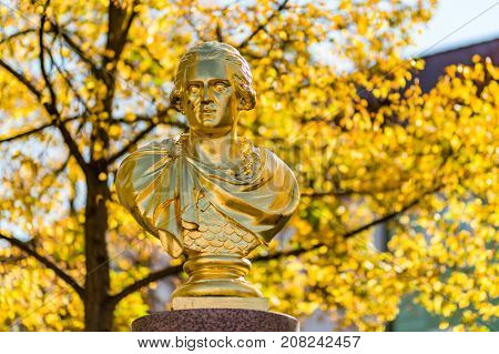 A golden statue with autumn trees in the background on the Old Town Square in Bischofswerda, Germany.
