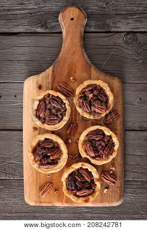 Mini Pecan Pie Tarts On A Wooden Paddle Board Against A Rustic Wood Background