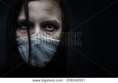 wounded woman with wounded face on black background with copy space looking at camera