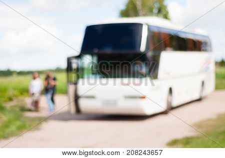 Blurred image of a large white tourist buses and a group of travelers next to him, summer bus tours and travel background