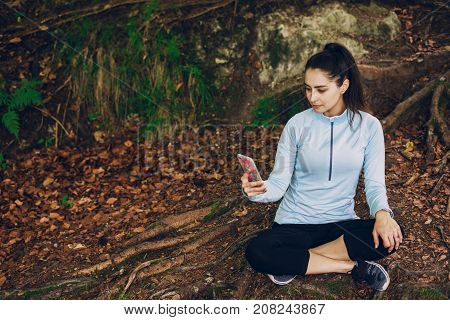 beautiful girl in a tracksuit sitting in green forest with phone