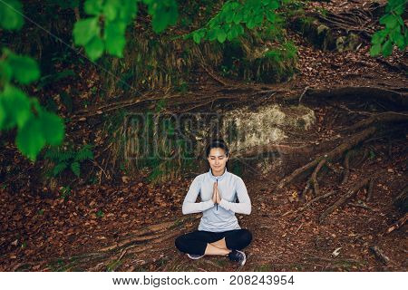 beautiful girl in a tracksuit sitting in green forest