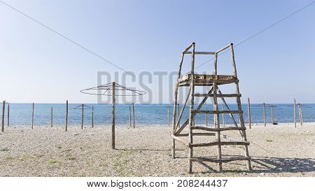 Not a season on a sandy beach a blue sea and a wooden derrick and beach umbrellas