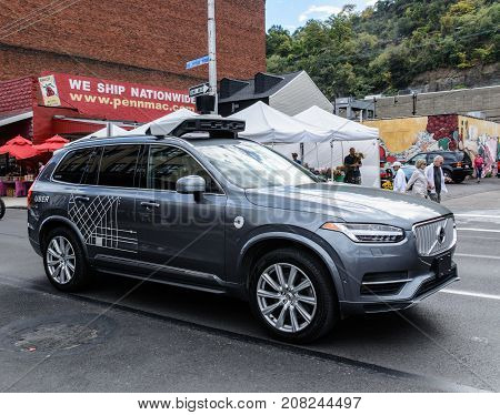 October7, 2017, Pittsburgh, Pennsylvania - An autonomous UBER test vehicle, with backup human driver inside, navigates the Strip shopping district on a busy Saturday morning.