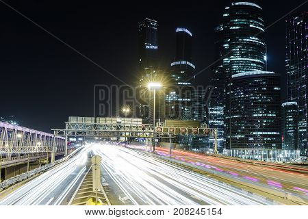 Skyscraper and transport metropolis traffic and blurry lights of cars on multi-lane highways and road junction at night in Moscow