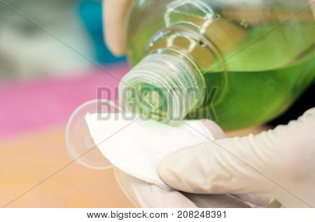 Hands with medical gloves holding a bottle with lotion and cotton pad.