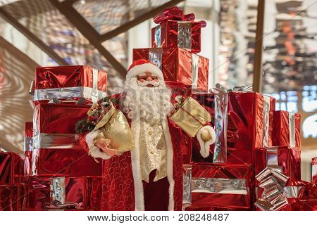 Big Cheerful Santa Claus doll Santa Claus and many red gift boxes with ribbons and on shiny background. Christmas background, presents, shoping concept. Generous Christmas.