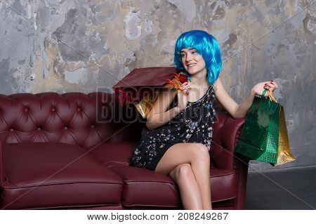 Woman with bags sitting on sofa on grunge wall. Fashion girl smiling in blue wig. Shopping commerce and retail concept. Consumerism and consumption.