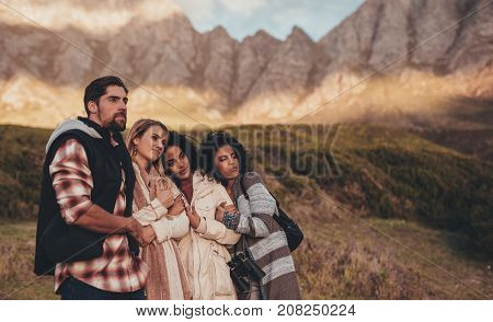 Friends on holiday looking at a landscape. Group of man and women standing together on roadtrip admiring a view in countryside.