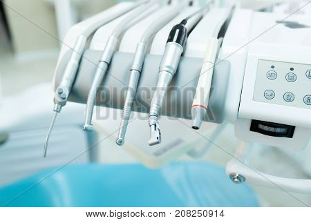 Various professional dental tools for good work with patients on the background of the patient's blue chair