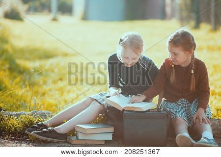 Adorable old-fashioned happy little 6 years old and 10 years old girls reading and smiling back to school chalkboard. Preschooler and schoolgirl sisters schoolkids.
