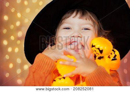 Adorable happy toddler girl decorating house with jack-o-lantern garland happy halloween beautiful warm lightings art photo.