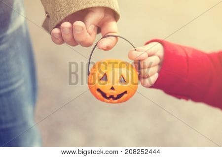 Little girl and her father Halloween parent and child trick or treating together. Toddler kid with jack-o-lantern. Kid with candy bucket closeup. Cold autumn day warm red coat. Toned photo.