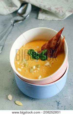 Autumn cream of pumpkin soup with bacon and croutons on a light background. Light dinner