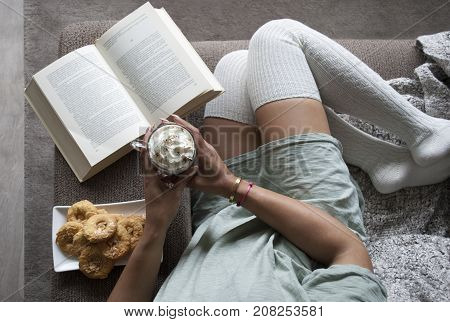 pretty girl reading book at home on couch with hot chocolate milk and cookies