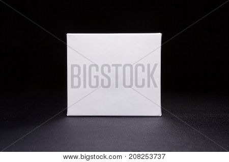 Blank medium size medicine from white paper packaging box for cosmetics, vitamins, pills or capsules. Packaging on dark blue background. Mock up