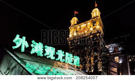 Shanghai, China - Nov 4, 2016: The Bund Tourist Tunnel (Chinese) entrance/exit by night. North China Daily News (AIA - American Insurance Association) building at back. On Zhongshan East 1st Road.
