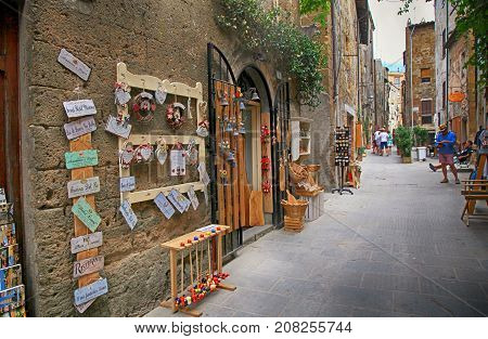 PITIGLIANO, ITALY - JULY 26, 2017: Narrow alley with gift shop in gorgeous etruscan and medieval town Pitigliano built of tuff stone, Tuscany, Italy. Called