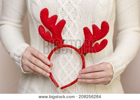 Detail of young female hands holding antlers on a headband