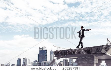 Businessman walking blindfolded on concrete bridge with huge gap as symbol of hidden threats and risks. Cityscape view on background. 3D rendering.
