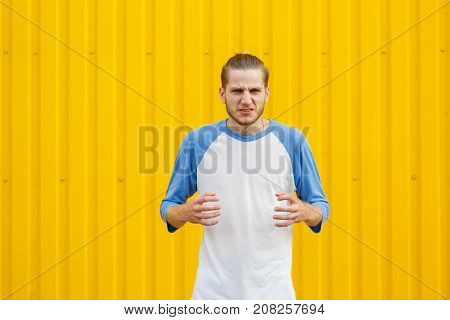 Disgusted, upset and disappointed young man in a loose shirt on a yellow wall background. Human face expressions. Copy space.