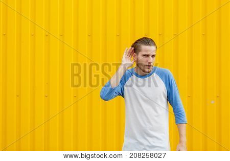 Casual and curious young man trying to overhear a conversation, touching his ear on a yellow wall background. Human face expressions. Copy space.