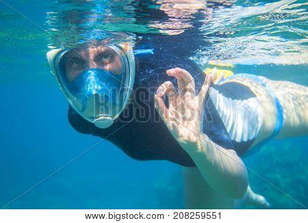 Woman snorkeling in blue water shows ok by fingers. Snorkeling in full face mask. Beautiful girl in water. Underwater photo of snorkel. Undersea swimming. Summer vacation. Water sport in tropic sea