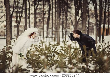 A Beautiful Ginger Bride In A White Fur Coat And A Groom Are Looking To Each Other Behind The Branch