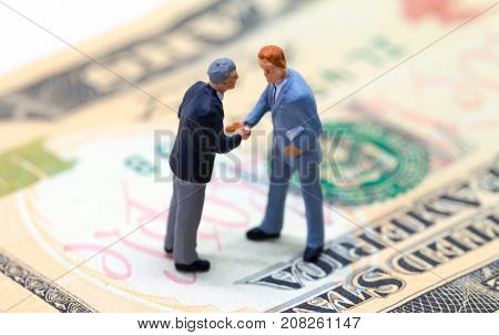 Businessmen shaking hands on american dollar. Tiny businessmen figurines on money background. Finance or economic growth concept. Making profitable deal. Buy and sell transactions for cash money