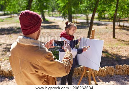 A guy in a brown jacket and a red hat makes a photo of how the young blonde artist works