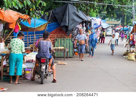 Dauin Philippines - 9 September 2017: Provincial filipino street market. Asian village streetlife. Rustic village road with stores and local people walking. Simple filipino people daily lifestyle