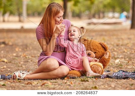 Gorgeous young mother playing with adorable little daughter with a huge plush teddy bear on a blurred autumn park background.
