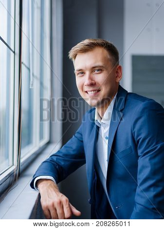 Positive and joyful young man in a classy, formal suit smiling on a blurred office background. Confident business worker. Copy space.