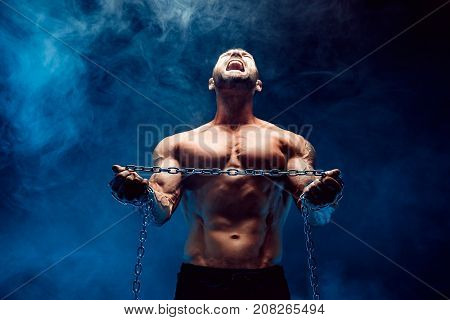 Shirtless bodybuilder man standing with chain and screaming. Try to break the chain. Selective focus on chain