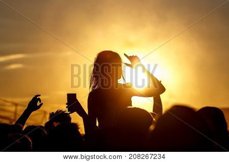 Girl cheering at outdoor music, rock festival