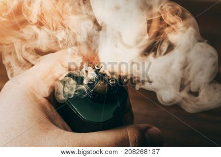 Clouds of vapor from RDA for vaping in man hand, modern vape electronic or ecig device, toned