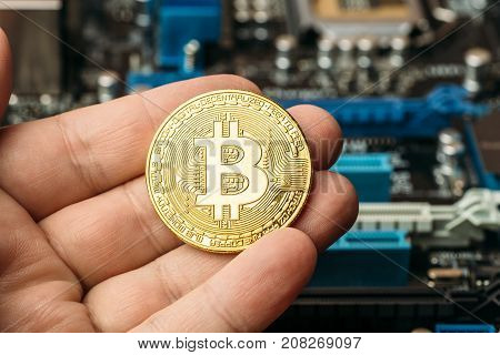 Gold coin of crypto currency Bitcoin in man hand