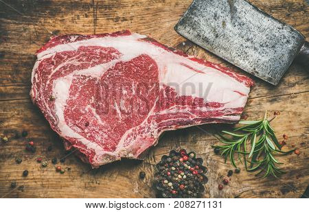 Flat-lay of raw uncooked prime beef meat dry-aged steak rib-eye on bone with seasoning and chopper knife on rustic wooden board background, top view. Meat high-protein dinner concept