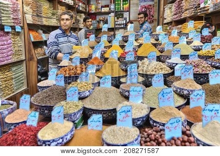 Fars Province Shiraz Iran - 19 april 2017: A shop with spices grains and dried fruits the seller stands next to the shop window.