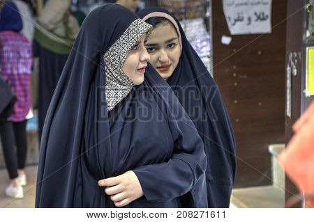 Fars Province Shiraz Iran - 19 april 2017: Two young Iranian girls in black Muslim clothes are walking along the city street.