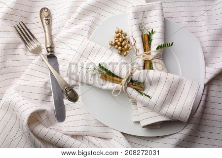 elegant place setting white, napkins decorated with cinnamon, and gold with garland of green leaves