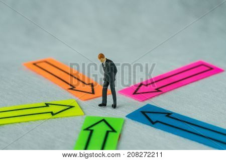 Miniature people figure businessman standing at the center of arrows pointing to him in all directions as business decision or people center concept.