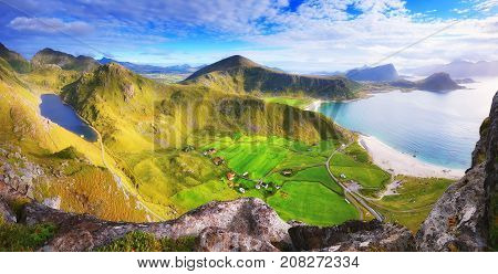 Sunny autumn day in Norway. Green valleys and mountain lake in sunlight. Lofoten landscape view from rock peak.