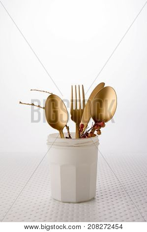 Festive golden cutlery knife and fork spoon in a white bottle on a light background