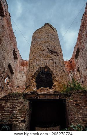 Old industrial furnace ruin in abandoned red brick factory