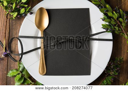 Christmas place setting menu, and gold spoon, from above