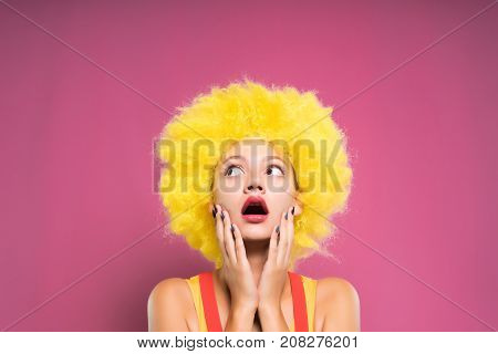 a clown of a girl looks surprised in the face holding her face